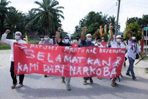 Puluhan warga saat membawa spanduk dalam aksi damai di Mapolsek Simpang Kanan, Jumat (02/07).